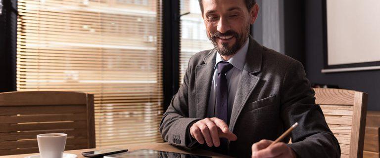 homme souriant remplit une certification papier