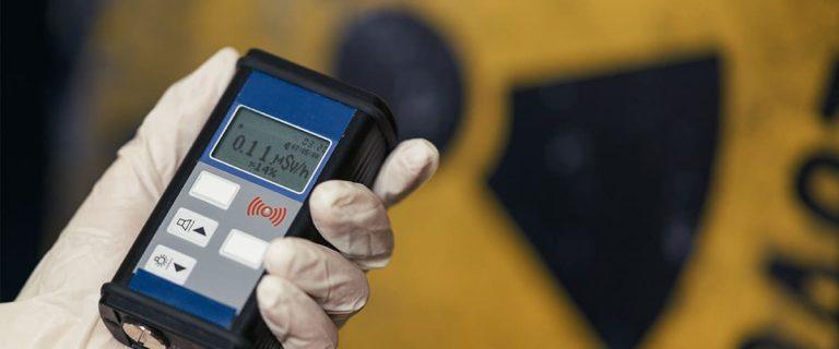 main qui tient un appareil de mesure radioactivité